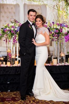 Bride and groom in front of wedding reception decor bolero strapless wedding dress katerina bocci