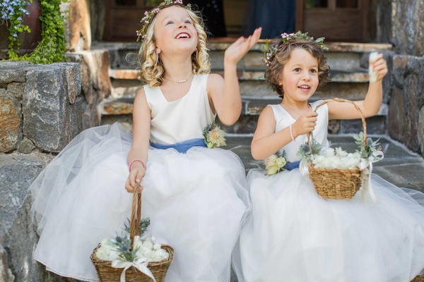 flower girls with baskets and flower crowns, white dresses with blue sashes