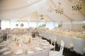 White drapery and chandeliers on ceiling of tented reception