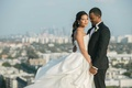Groom in tuxedo smiles at bride in Vera Wang bridal gown on rooftop of Four Seasons Los Angeles