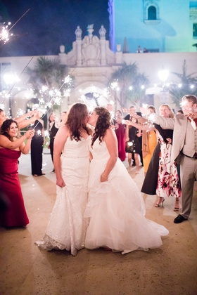same-sex wedding, lesbian wedding, bride in winnie couture kissing bride in hayley paige sparklers