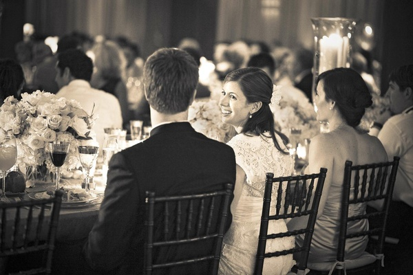 Black and white photo of bride and groom at head table