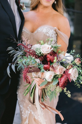 bride in blush off shoulder inbal dror wedding dress foliage fall bouquet burgundy flowers