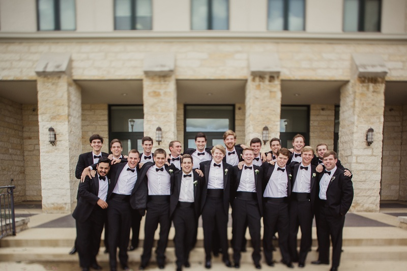 groom and groomsmen in tuxedos in front of Texas venue