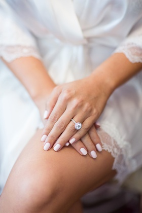 large diamond engagement with halo and thin band with pale pink manicure nails