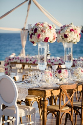 Wedding reception on stage over sand at beach wood tables white pink flowers ocean view