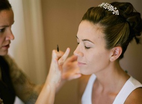 Bride with updo and tiara getting makeup done