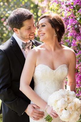 bride looks over shoulder at groom black tuxedo white wedding dress white bouquet gray tie
