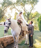 Bride in a Claire Pettibone dress with gold and silver embroidery sits on white horse, groom