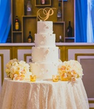 "four tier white wedding cake with floral appliques and a gold ""P"" cake topper"