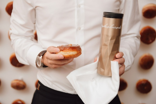 Wedding reception guest holding donut doughnut and coffee thermos take home favor late night snack