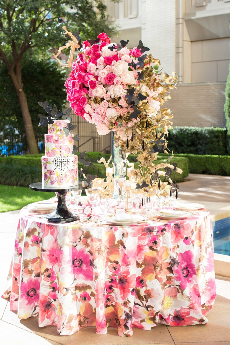 white cake with pink flower design and black jewels black butterflies floral linen rose centerpiece