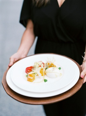 Wedding guest holding plate of salad course at spring wedding burrata cheese and heirloom tomato