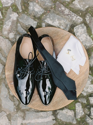 wedding accessories for groom wood table on cobblestone street in guatemala patent leather