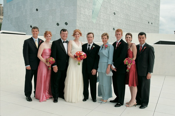 Wedding guests on rooftop with bride and groom