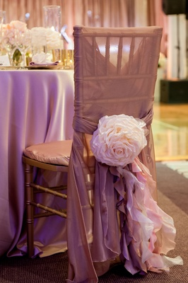 Gold chair wrapped with champagne sash and flower
