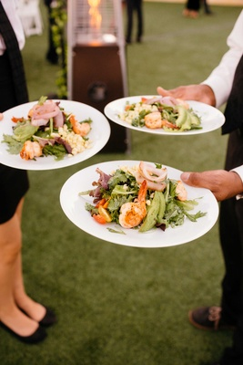 grilled shrimp salad, with lettuce servers holding plates