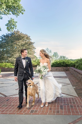 bride in flowing wedding dress with lace bodice and groom in tuxedo, walking dog