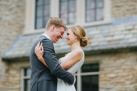 blonde bride with low chignon bun hugs groom in grey suit