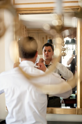 groom looks in mirror to adjust shirt collar and tie