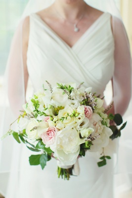 Bride in V-neck wedding dress holding flowers
