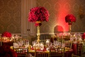 tall centerpiece of red roses held up by gold stand