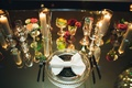 glass tableware and vases on mirrored tabletops bow napkin candlelit