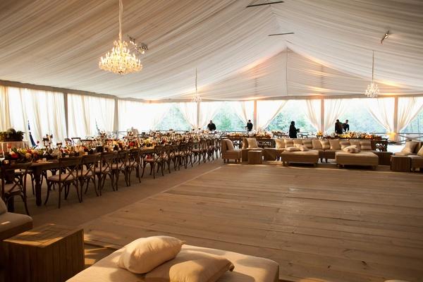 Wooden dance floor under chandelier in middle of tented wedding space