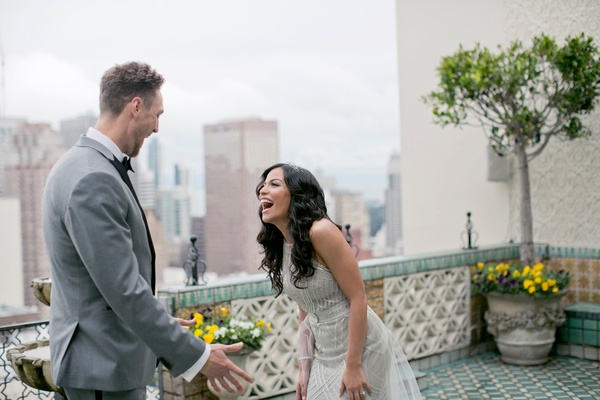 Alexis Cozombolidis and Hunter Pence during first look on balcony in san francisco skyline grey suit