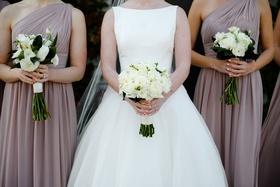 bride in bateau neckline wedding dress white rose bouquet bridesmaids mauve dresses white greenery