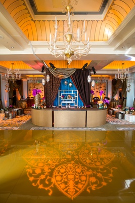 Moroccan-style engagement party with henna pattern projection on gold dance floor