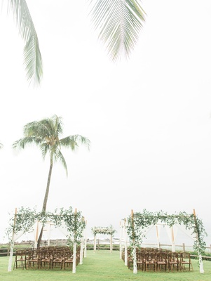 Wedding reception montage kapalua bay bamboo chairs green lawn arbor greenery wood structure outdoor