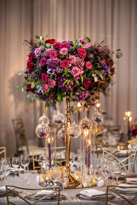 tall gold centerpiece with pink purple burgundy flowers greenery glass orbs taper candles