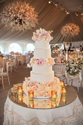 Mirror top cake table with five layer wedding cake with fresh flower layers in between