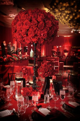 Tall black candlestick topped with red roses