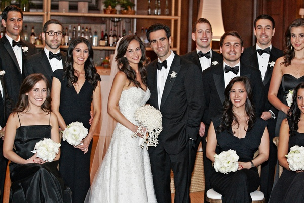 Bride and groom with tuxedo groomsmen and black dress bridesmaids