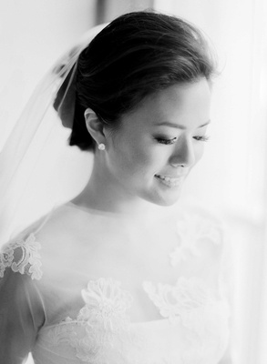 Black and white photo of bride with stud earrings, veil on updo, and lace Vera Wang wedding dress