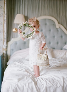 Flower girl on bed holding basket and daisy flower crown