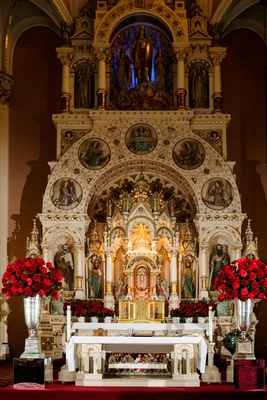 wedding ceremony beautiful catholic sanctuary altar red roses in silver urns arrangements