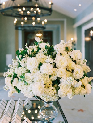 Wedding reception escort card table white flowers peony rose hydrangea green leaves tent cards