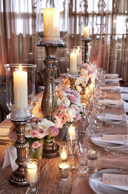 Wedding reception table with sequin runner, pink and white flowers, and candleholders