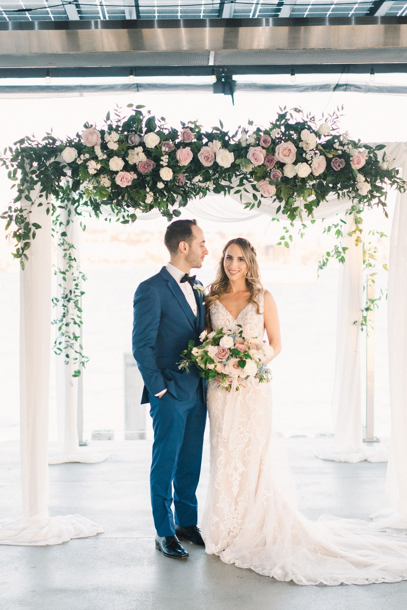 groom in cobalt blue suit looking at bride as they stand under chuppah with roses in shades of pink