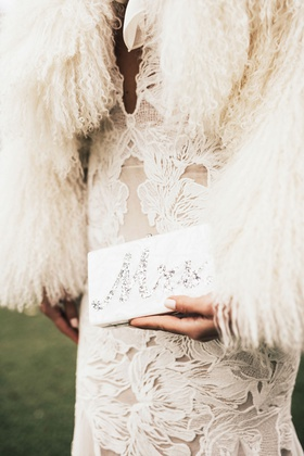 bride in wedding dress with fur wrap holding mother of pearl silver mrs edie parker wedding purse