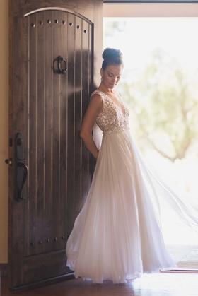 Bride by rustic door wearing Mira Zwillinger sheath wedding dress from Carine's Bridal Atelier bun