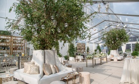 Beautiful cocktail hour lounge area white settees trees tables neutral color palette