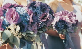 bridesmaids holding purple and blue flowers