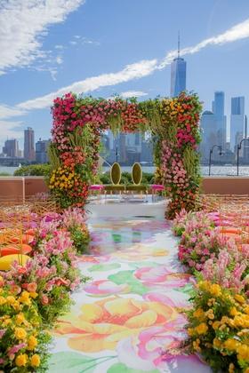 wedding ceremony new york city skyline pink yellow green flower print aisle chairs mandap