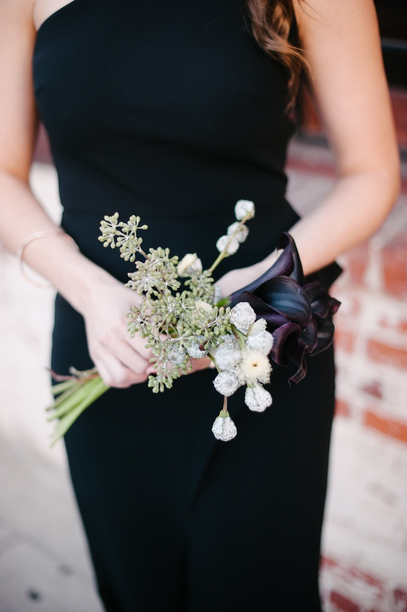 Bridesmaid in black dress holding midnight calla lily and weedy bouquet