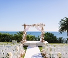 Wooden arbor with white fabric orchids and roses, ocean views bel-air bay club