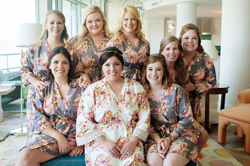 Bride in white flower print robe with lace hem and bridesmaids in grey robes with flower print